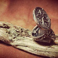 Anello porta veleno in metallo su legno