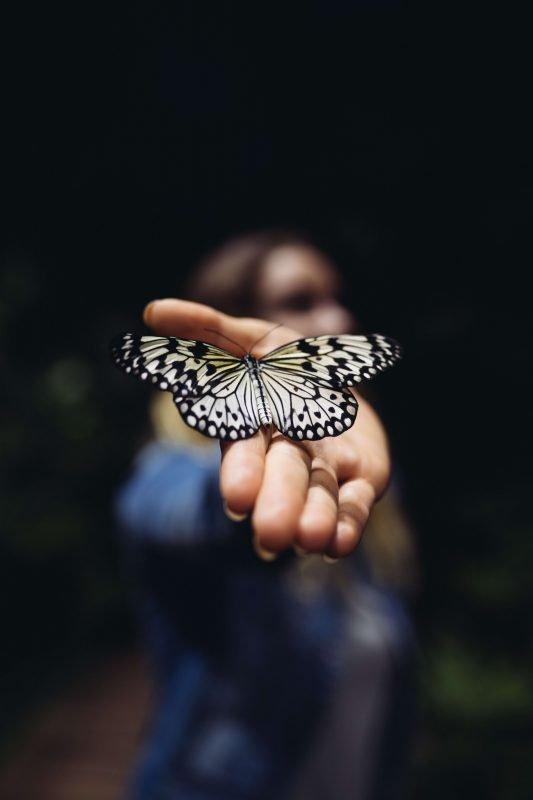 Una strega con una farfalla sulla mano